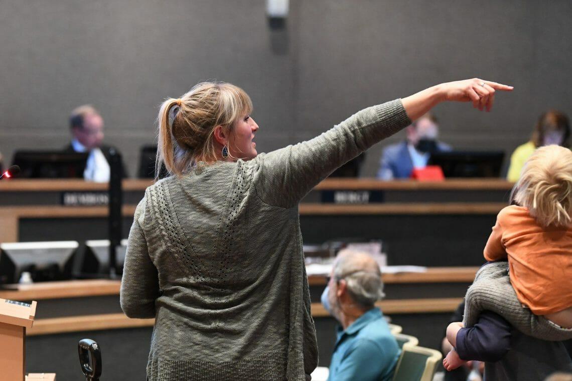A woman points toward an individual causing a disruption