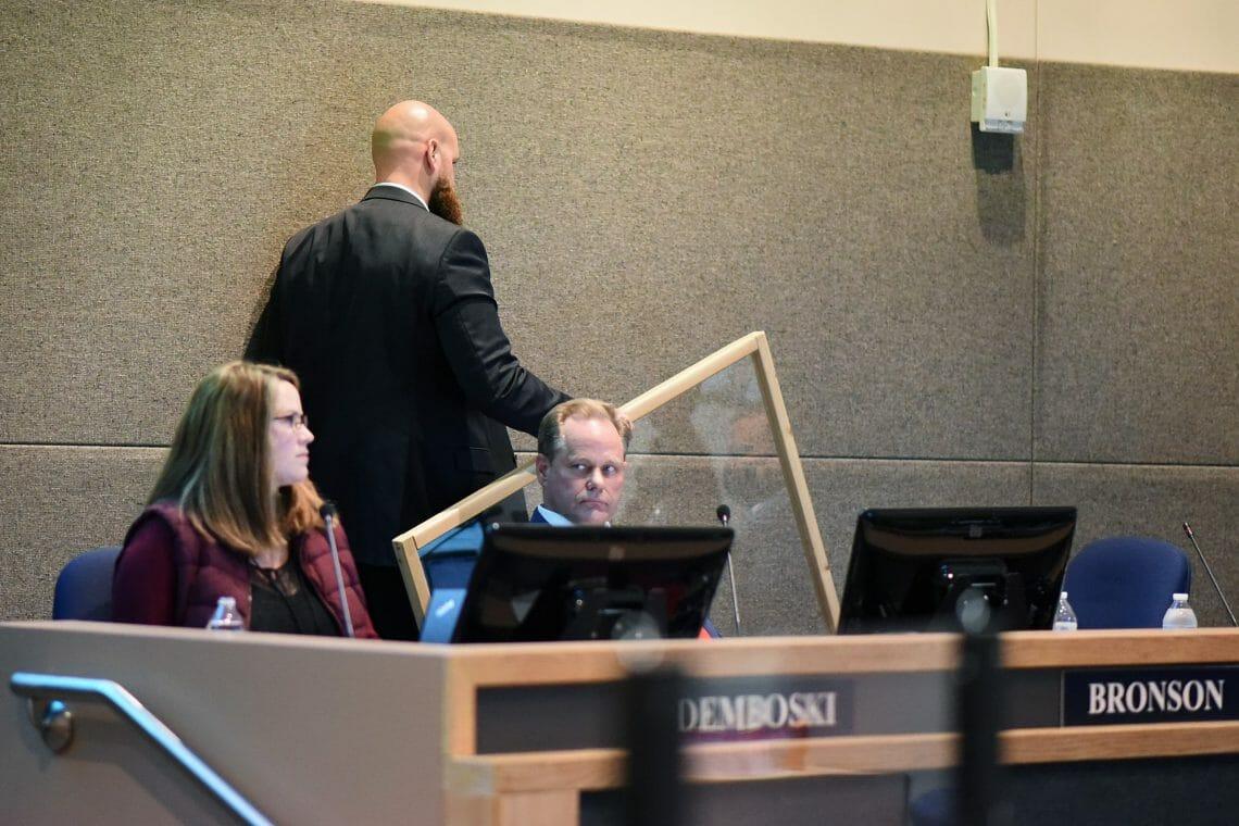 Adam Trombley removes the plexiglass shield from the podium where audience members provide testimony