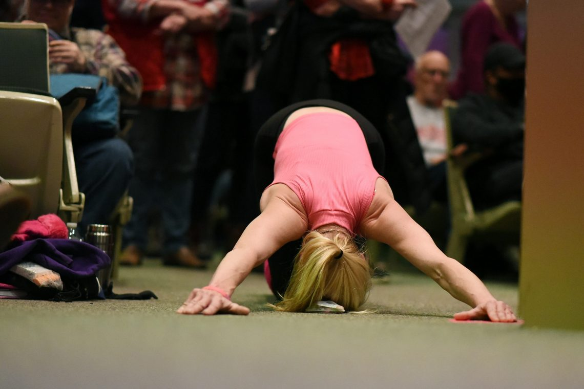 A woman does push-ups during audience testimony